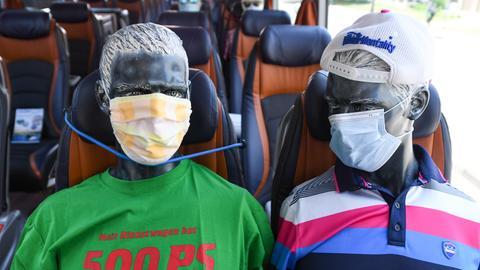 Leicht unheimlich: Schaufensterpuppen mit Mundschutz sitzen beim Aktionstag privater Busunternehmen in Wiesbaden in einem Reisebus.
