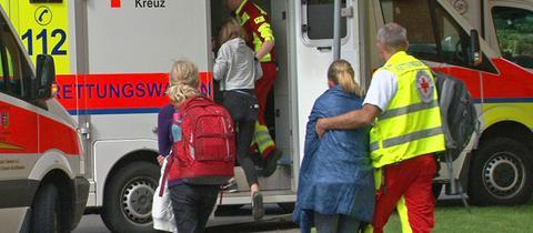 Ein Rot-Kreuz-Helfer bringt eine Schülerin zum Rettungswagen.