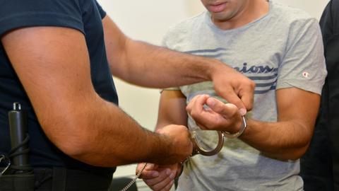 Der Angeklagte wird in den Saal des Landgerichts Hanau geführt und bekommt seine Handschellen abgenommen.