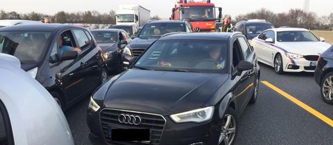 Viele Autos stehen durcheinander, im Hintergrund ein Feuerwehrfahrzeug.