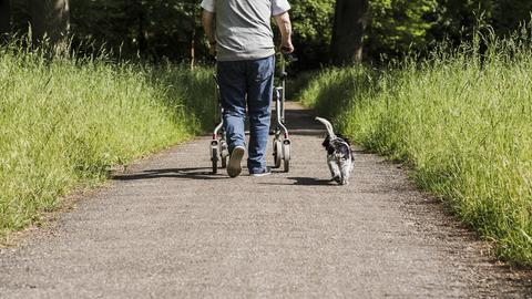 Mann mit Rollator und kleinem Hund