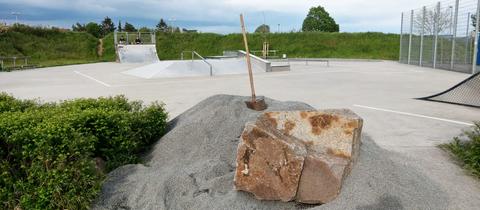 Foto des Skateparks in Dieburg - ohne Rollsplit. Im Vordergrund ein Haufen Rollsplitt, in dem eine Schaufel steckt. Im Hintergrund zwei Skater auf einer Halfpipe sitzend.