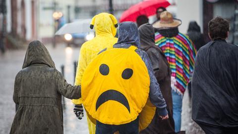 Karnevalisten gehen in Seligenstadt bei starkem Regen durch die Altstadt.