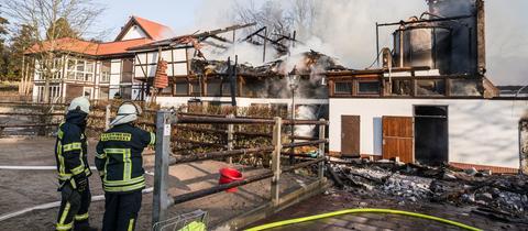 Feuerwehrleute stehen vor den rauchenden Trümmern eines Pferdestalls und einer Reithhalle.