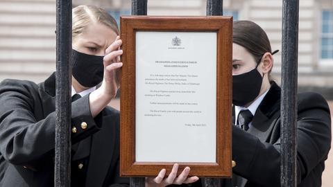 Mitarbeiterinnen hängen eine Tafel mit der Todesmitteilung des britischen Prinz Philip an das Tor des Buckingham Palace.