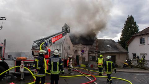 Feuerwehrleute und ein brennendes Haus.