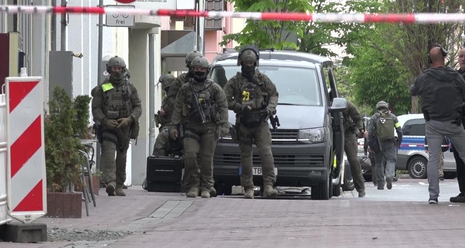 Polizisten eines Spezialeinsatzkommandos durchsuchen Teile der Rüsselsheimer Innenstadt nach Hinweisen auf die Schießerei