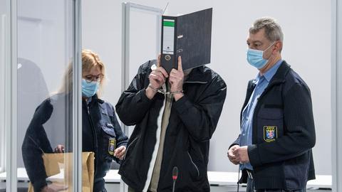 Angeklagter mit Ordner über dem Kopf, neben ihm stehen zwei Polizisten.
