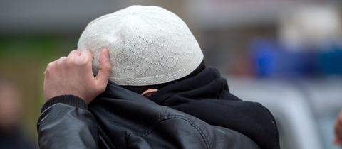"""Mit seiner Jacke verdeckt ein ein Mann aus dem Umfeld der Koran-Verteilaktion """"Lies"""" auf der Frankfurter Zeil sein Gesicht."""