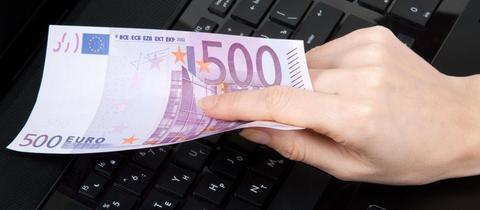 Eine weibliche Hand hält über einer Computertastaur einen 500-Euro-Schein