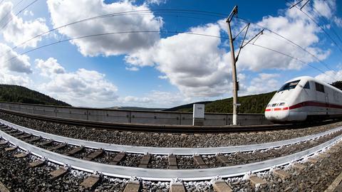 Ein ICE der Deutschen Bahn fährt an einem Gleis mit weißem Farbanstrich vorbei.