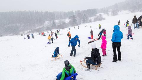 Rodler auf einer verschneiten Piste bei Schmitten im Taunus.