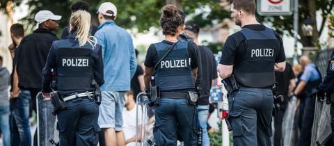 Polizisten in Darmstadt bewachen nach dem Schlossgrabenfest eine Gruppe festgesetzter junger Männer neben dem Herrngarten