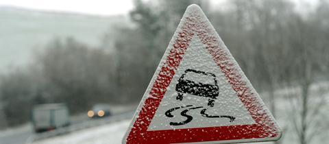 Verschneites Straßenschild warnt vor Rutschgefahr.