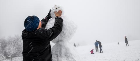 Ein Mann beut einen Schneemann auf dem Großen Feldberg.