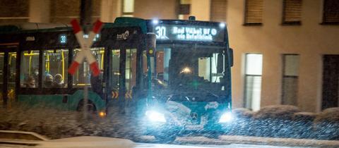 Ein mit einigen Fahrgästen besetzter Bus ist im morgendlichen Berufsverkehr bei Schneetreiben auf der Friedberger Landstraße unterwegs.
