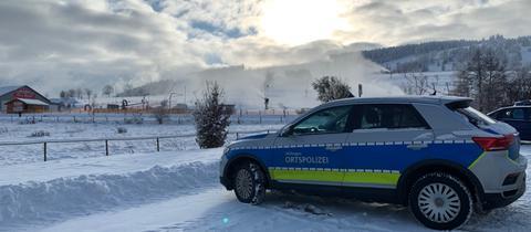 Ein Polizeiauto steht auf einem Parkplatz in einer verschneiten Landschaft