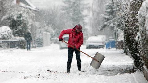 Eine Frau schippt Schnee