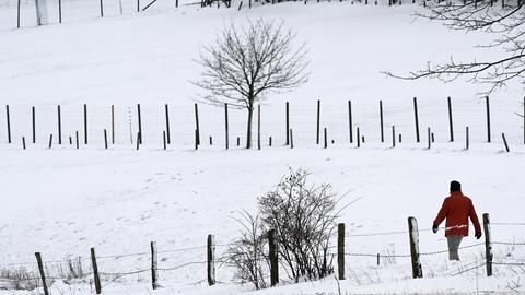 Ein Mann geht durch eine verschneite Landschaft an einem Zaun entlang.