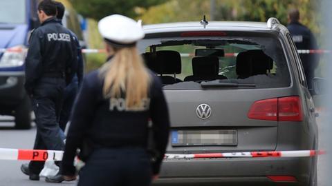 Ein ziviles Polizeifahrzeug mit zerstörter Heckscheibe steht in hinter einem Absperrband