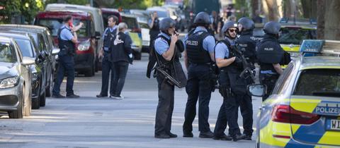 Schwer bewaffnete Polizisten sichern nach einer Schießerei ein Wohngebiet in Darmstadt-Kranichstein.