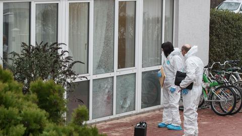 Ermittler stehen vor der von Schüssen getroffenen Fensterfront.
