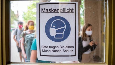 Schüler mit Masken vor einem Hinweisschild zur Maskenpflicht