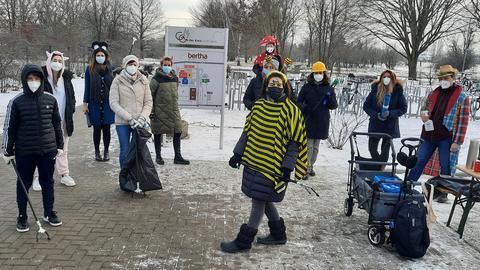 Kinder und Lehrkräfte sammeln Müll vor der Gesamtschule in Mörfelden-Walldorf.