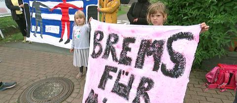 """Zwei Kinder halten ein selbstgemaltes Plakat hoch, auf dem """"Brems für mich"""" geschrieben steht. Im Hintergrund weitere Kinder, Eltern und selbstgebaute Plakate."""