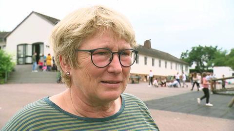 Die Schulleiterin Brigitte Trietsch mit kurzen Haaren, Brille und grün-gestreiftem T-Shirt spricht in die Kamera. Im Hintergrund ist der Schulhof mit spielenden Kindern zu sehen.