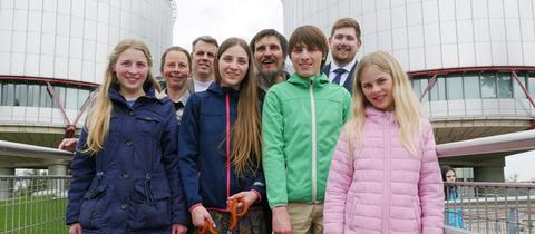 Dirk (Mitte) und Petra Wunderlich (2.v.li.) stehen mit ihren vier Kindern und ihren beiden Rechtsbeiständen vor dem Europäischen Gerichtshof für Menschenrechte.