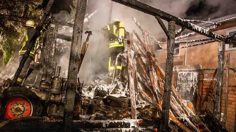 Ein Feuerwehrmann steht inmitten des abgebrannten Schuppens