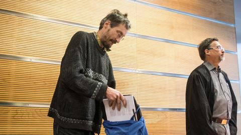 Ein Mann holt Akten aus einem blauen Stoffbeutel, daneben ein weiterer Mann im Talar.