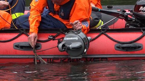 Einsatzkräfte des THW lassen einen Tauchroboter zu Wasser.