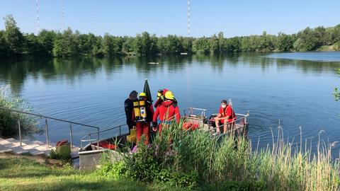 Ein Boot mit Einsatzkräften am Ufer eines Badesees