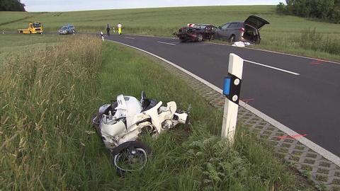 Motorroller und zwei Unfallautos auf Kreisstraße