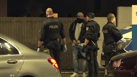 Polizisten und ein vermummter Angreifer stehen auf der Straße.