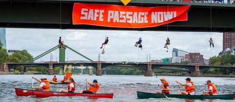 Boote auf dem Main, Brücke, abgeseilte Menschen mit Transparent