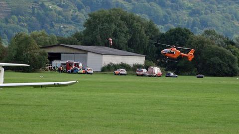 Helikopter landet neben Rettungskräften auf dem Flugplatz.