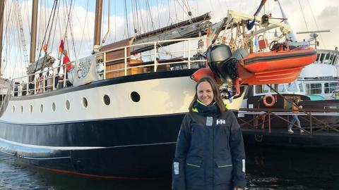 Carla von Glasow steht vor dem Segelschif, mit welchem sie die Reise nach Chile zur Klimakonferenz antreten wird.