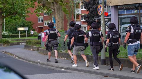 Sechs Polizeikräfte laufen über eine Straße.