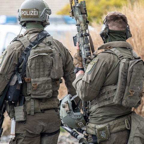 """Zwei Beamte eines Spezialeinsatzkommandos (SEK) der Frankfurter Polizei in voller Ausrüstung von hinten. Eine Person trägt einen Helm, auf dem """"Polizei"""" steht, die andere ist ohne Helm und trägt ein großes Maschinengewehr."""