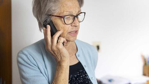 Eine Seniorin steht in ihrem Wohnzimme und hält ein Telefon an ihr Ohr.