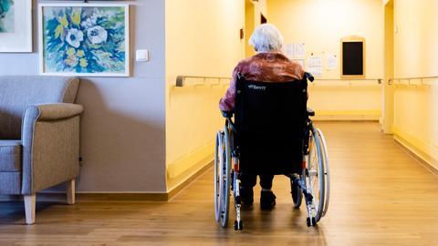 Eine ältere Frau sitzt im Rollstuhl, sie ist alleine.