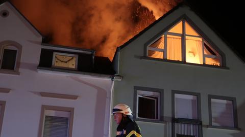 Ein Feuerwehrmann läuft an dem brennenden Haus vorei