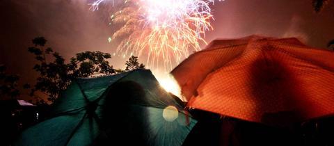 Zwei Menschen betrachten unter Regenschirmen ein Feuerwerk.
