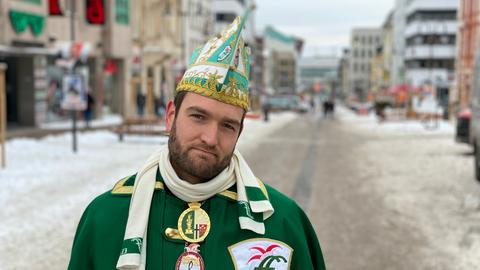 Ein Fuldaer Karnevalist steht traurig auf der Straße, weil der Rosenmontagszug wegen Corona abgesagt wurde.