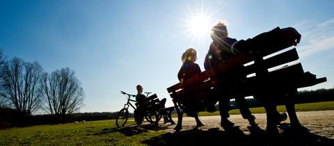 Menschen sitzen in der Sonne auf Parkbänken
