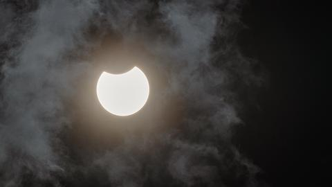 Der Mond verdeckt einen Teil der Sonne.