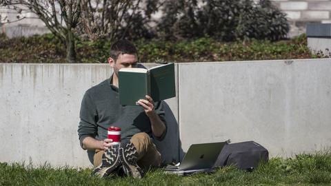 Ein Mann ließt ein Buch von Schiller in der Sonne